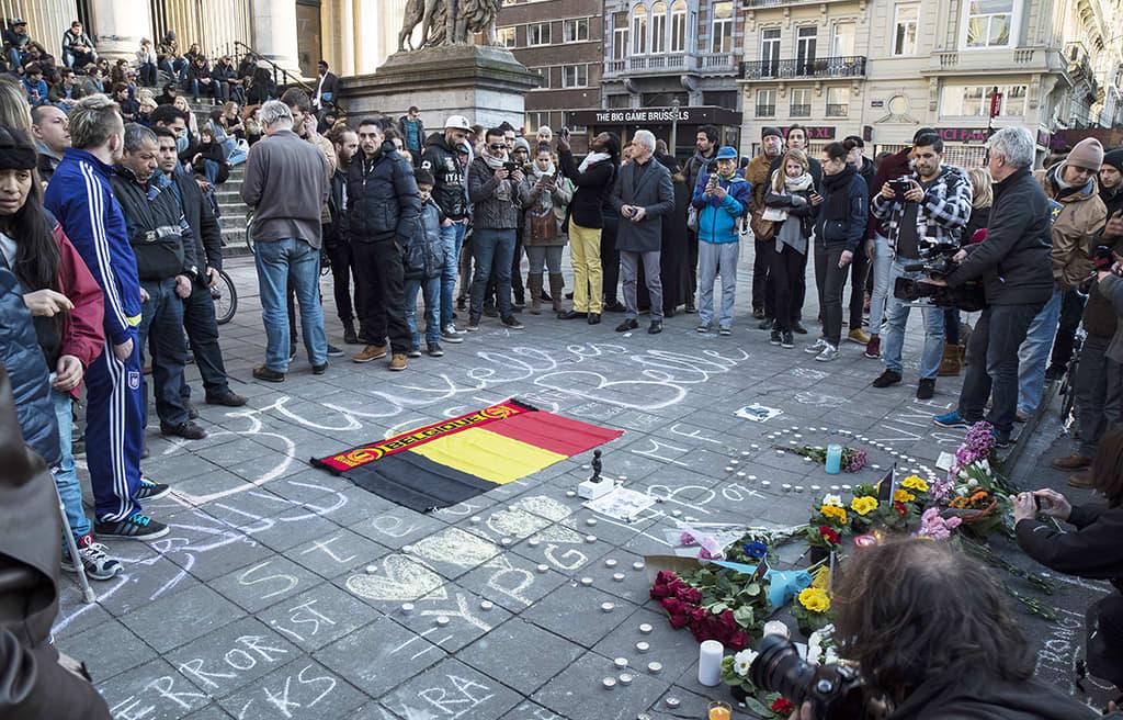 Ihmisiä kokoontuneena maassa olevan Belgian lipun ympärille Brysselissä.