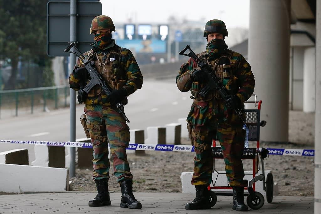 Kaksi raskaasti aseistettua univormupukuista, naamioitua sotilasta lentokentän edessä.