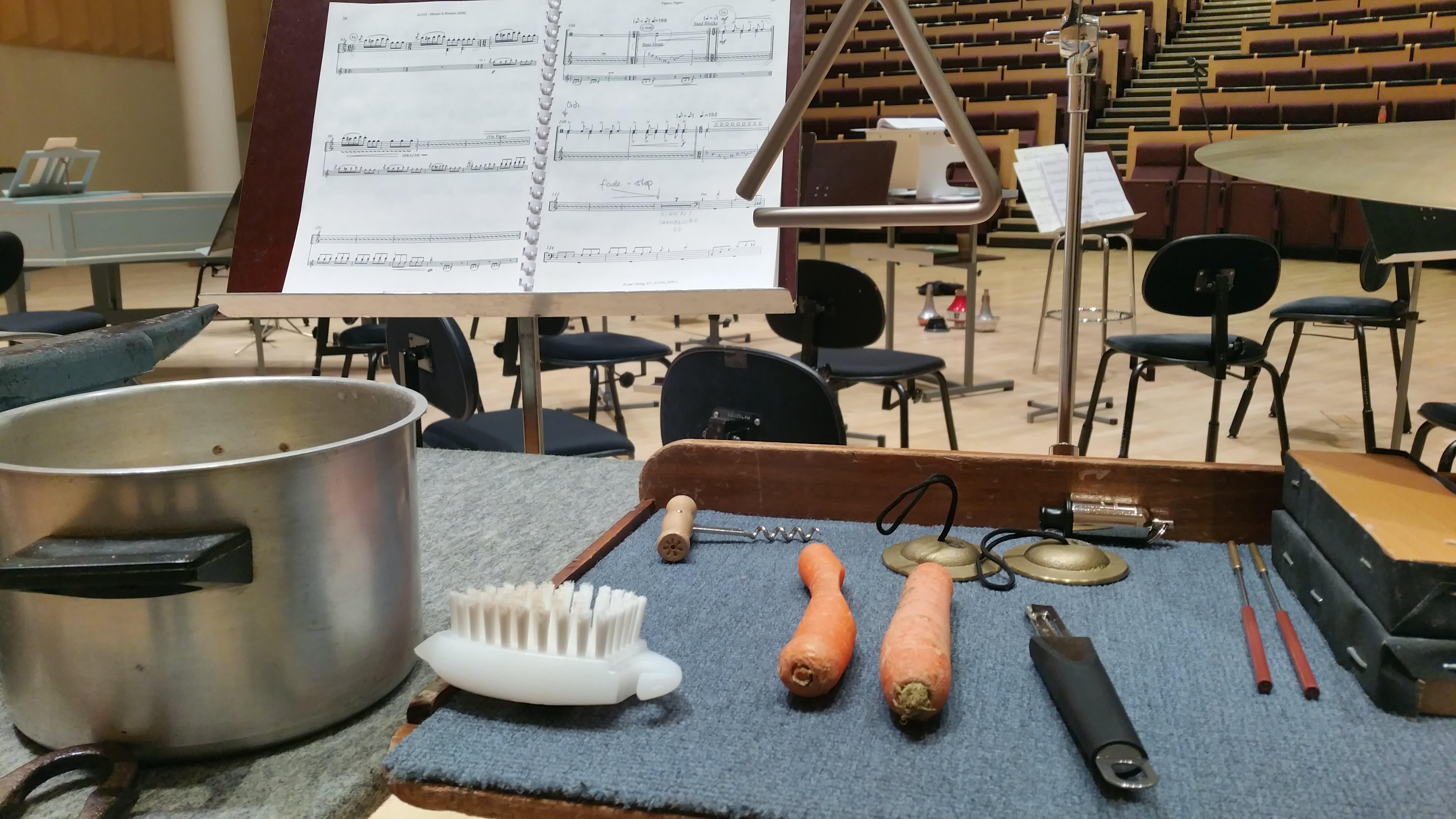 Kattila, porkkanat, juuresharja ja muita keittiötarvikkeita konserttisalissa.