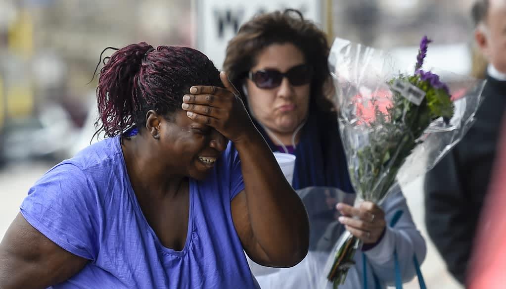 Itkevä nainen painaa kämmentä otsaansa. Taustalla toinen nainen, jolla on kukkakimppu kädessään.