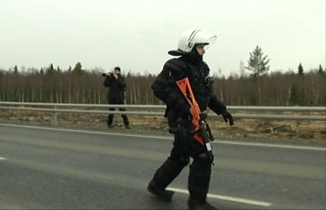 Poliisi kantaa projektiiliasetta Pyhäjoen Hanhikivenniemen ydinvoimalatyömaan mielenosoituksissa.