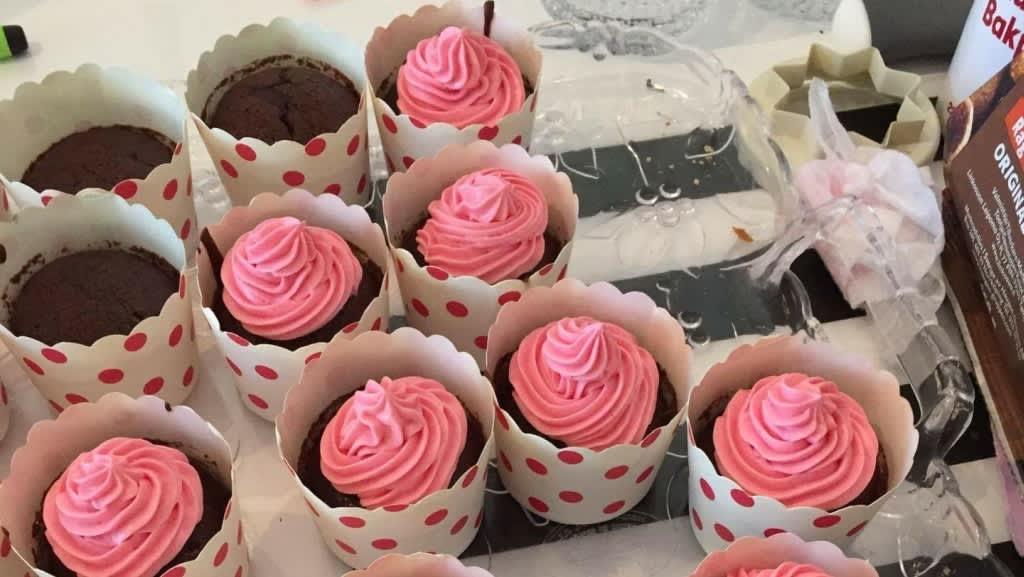 Muffinseja lautasella. Osa koristelu vaaleanpunaisella kreemillä.