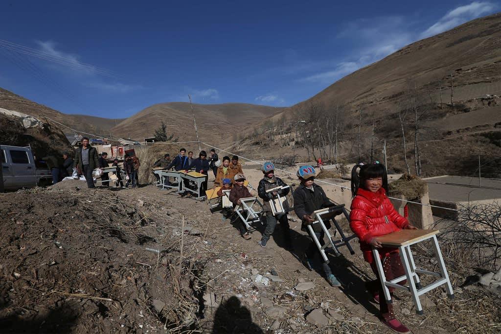 Lapset kantavatat lahjoituksina saamiaan pulpetteja Dingxissä Gansun maakunnassa maaliskuussa 2016.