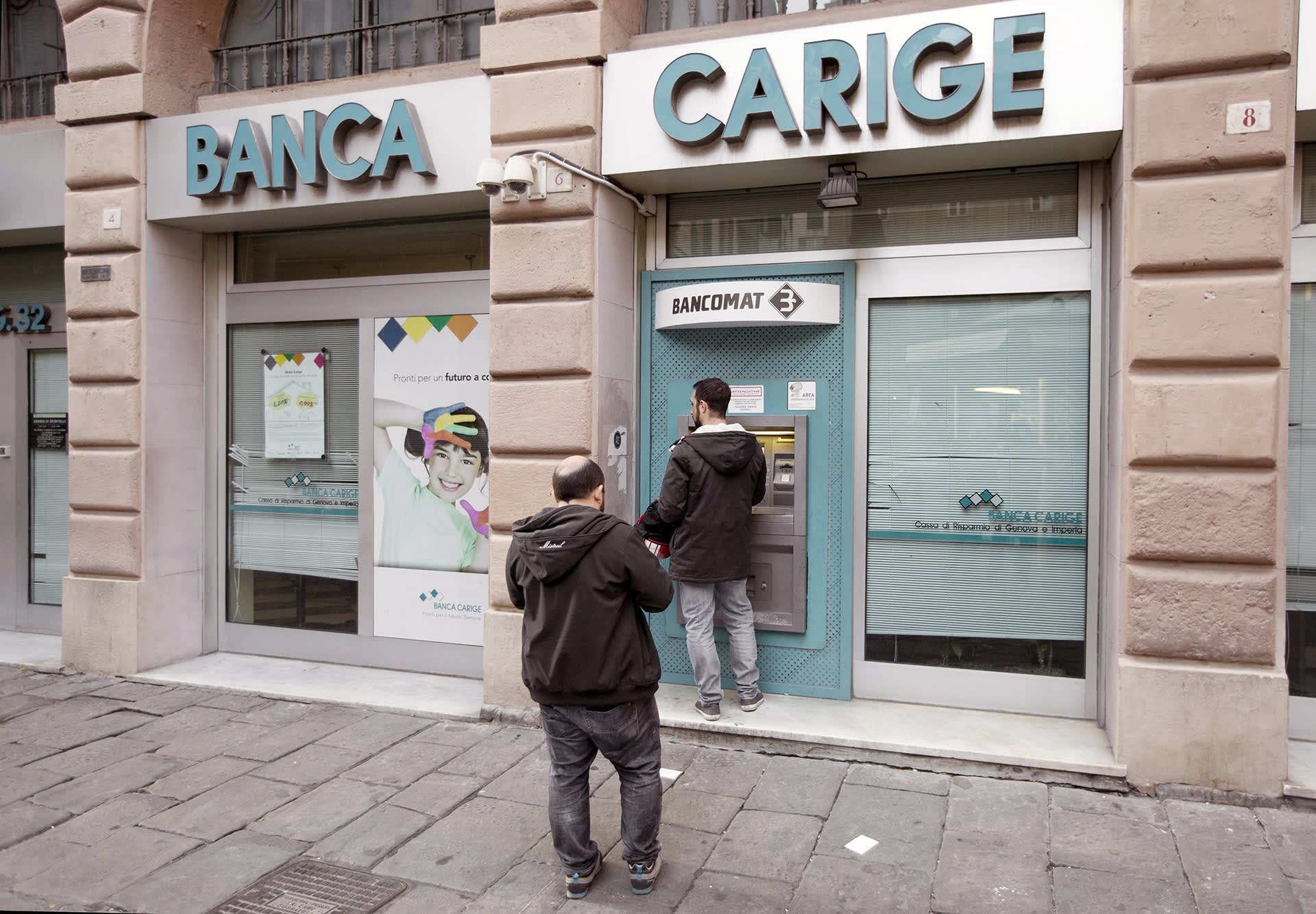 Asiakkaat jonottavat pankkiautomaatille Italian Genovassa.
