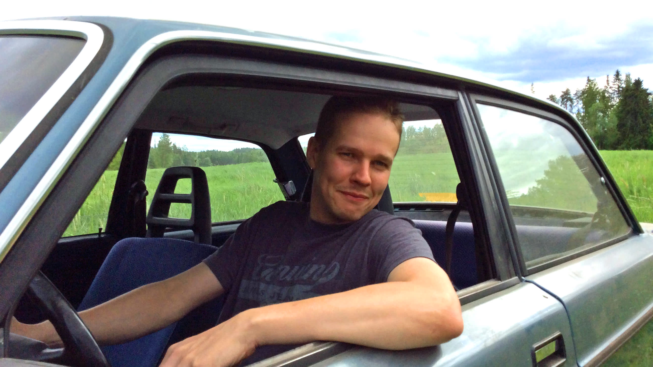 Pekka Holmström istuu autossa ikkuna auki ja käsi ikkunan pielen päällä.