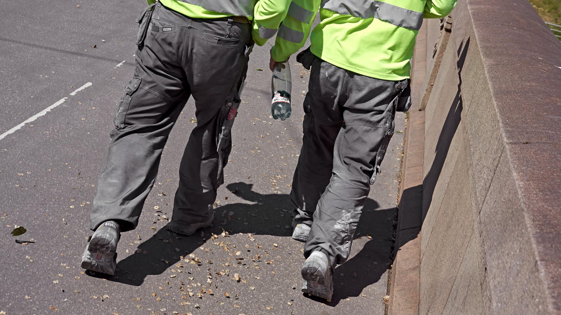 Kaksi työmiestä kävelee kadulla.