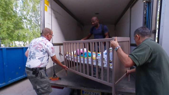 Kolme miestä siirtää lapsen sänkyä kuljetusauton kyytiin.