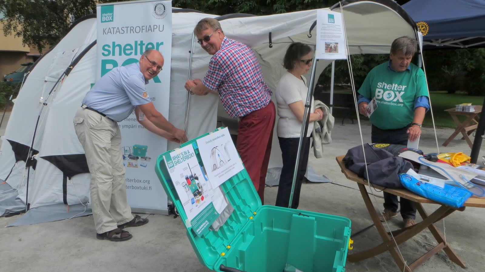 Vihreä shelter box muovilaatikko sisältää kodin. Teltan naruja kiristävät Pekka Huovila ja Tapio Vihersaari.