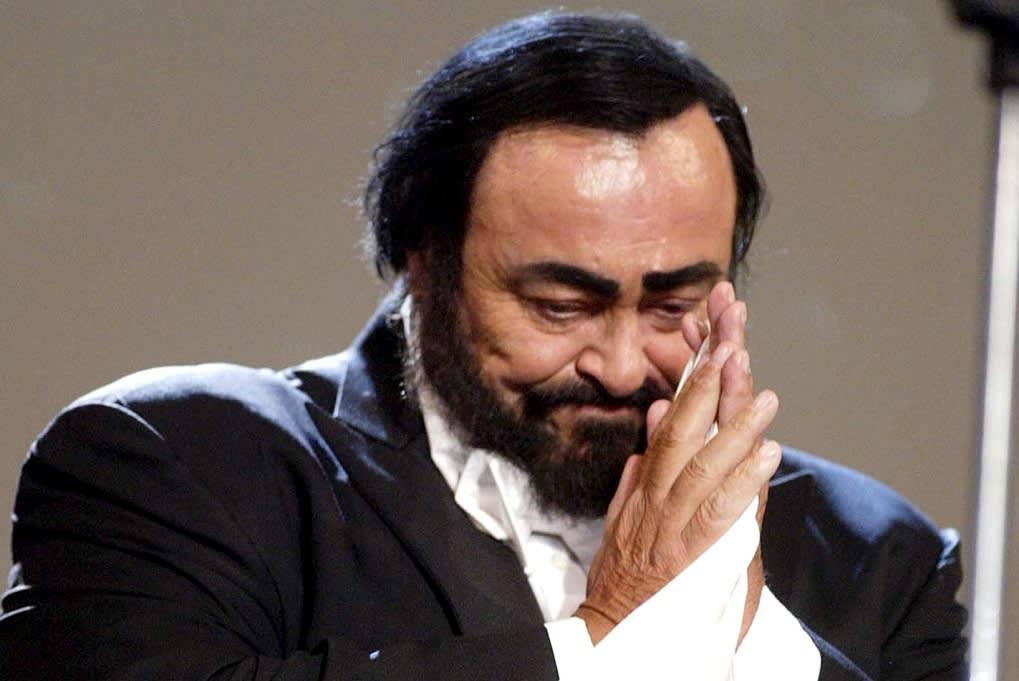 Pavarotti kumartaa yleisölle kädet yhdessä.