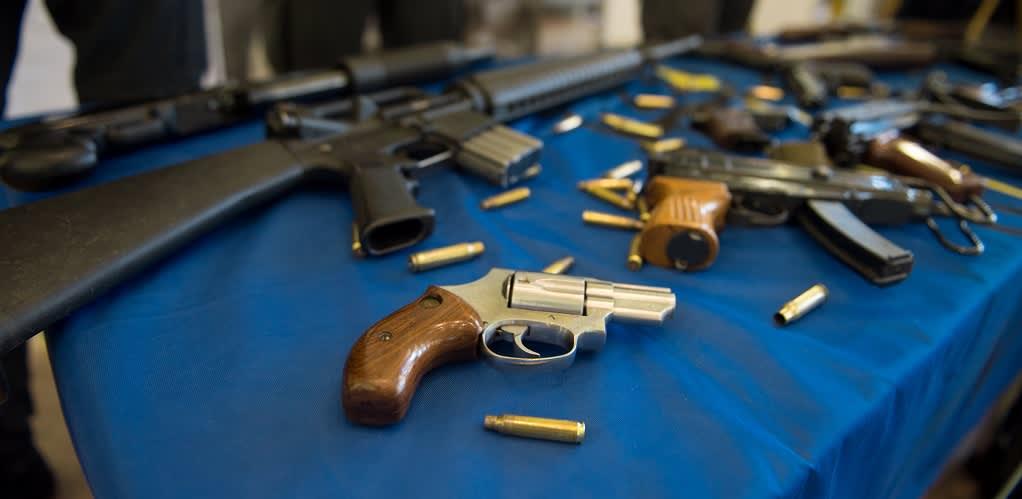 Aseita ja ammuksia pöydällä.