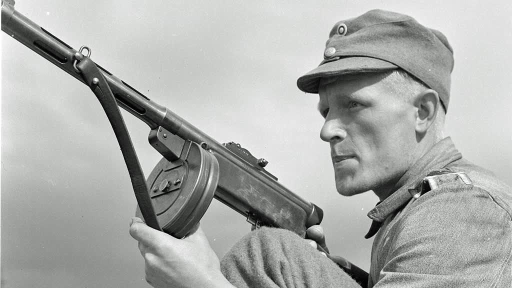 Mies suomalaisessa sotilaspuvussa konepistoolin kanssa.