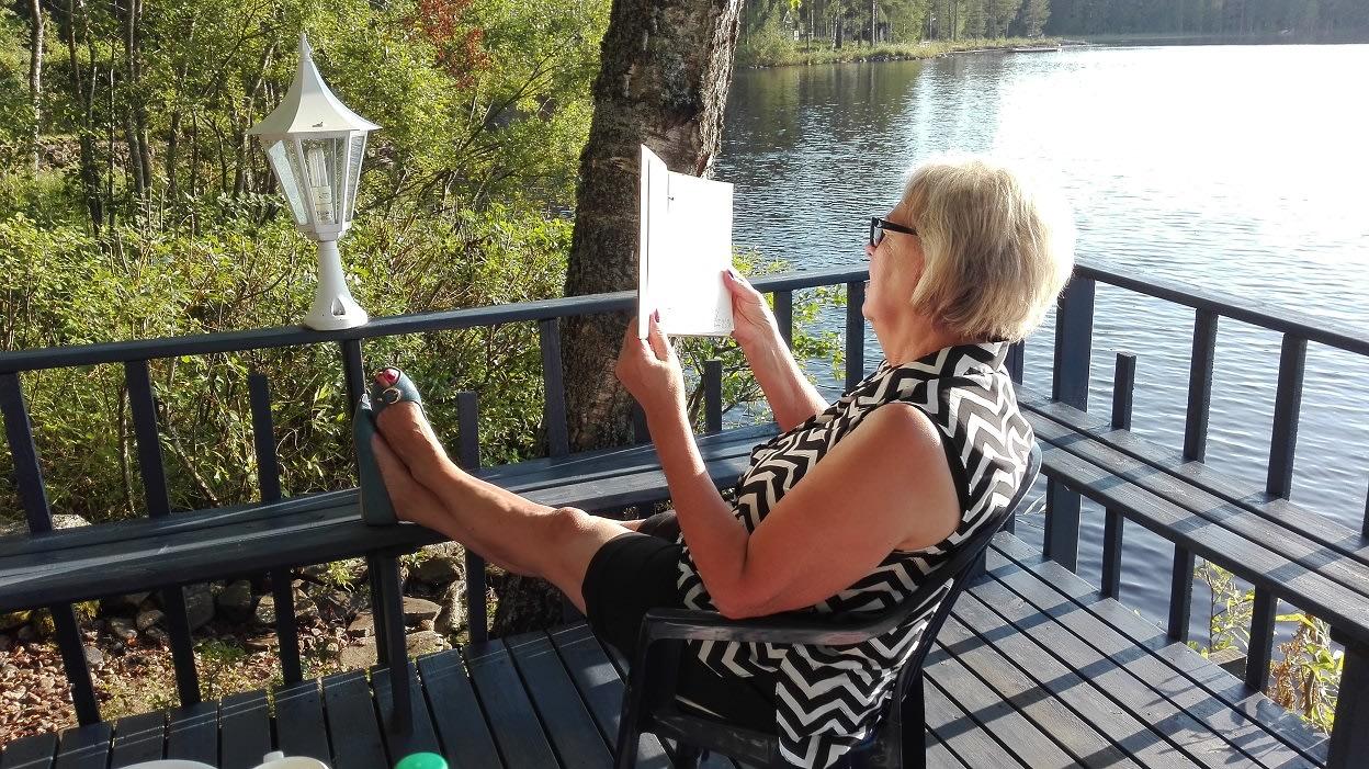 Saara isoniemi lukee mökkikirjaa
