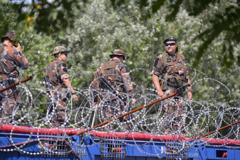 Unkarilaiset sotilaat partioivat Serbian vastaiselle rajalle pystetyn aidan luona heinäkuussa.