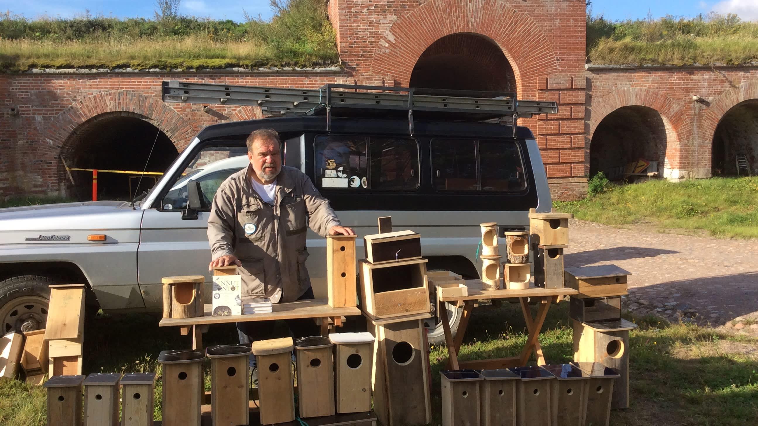 Urpo Koponen seisoo linnunpönttöjen takana Kyminlinnassa