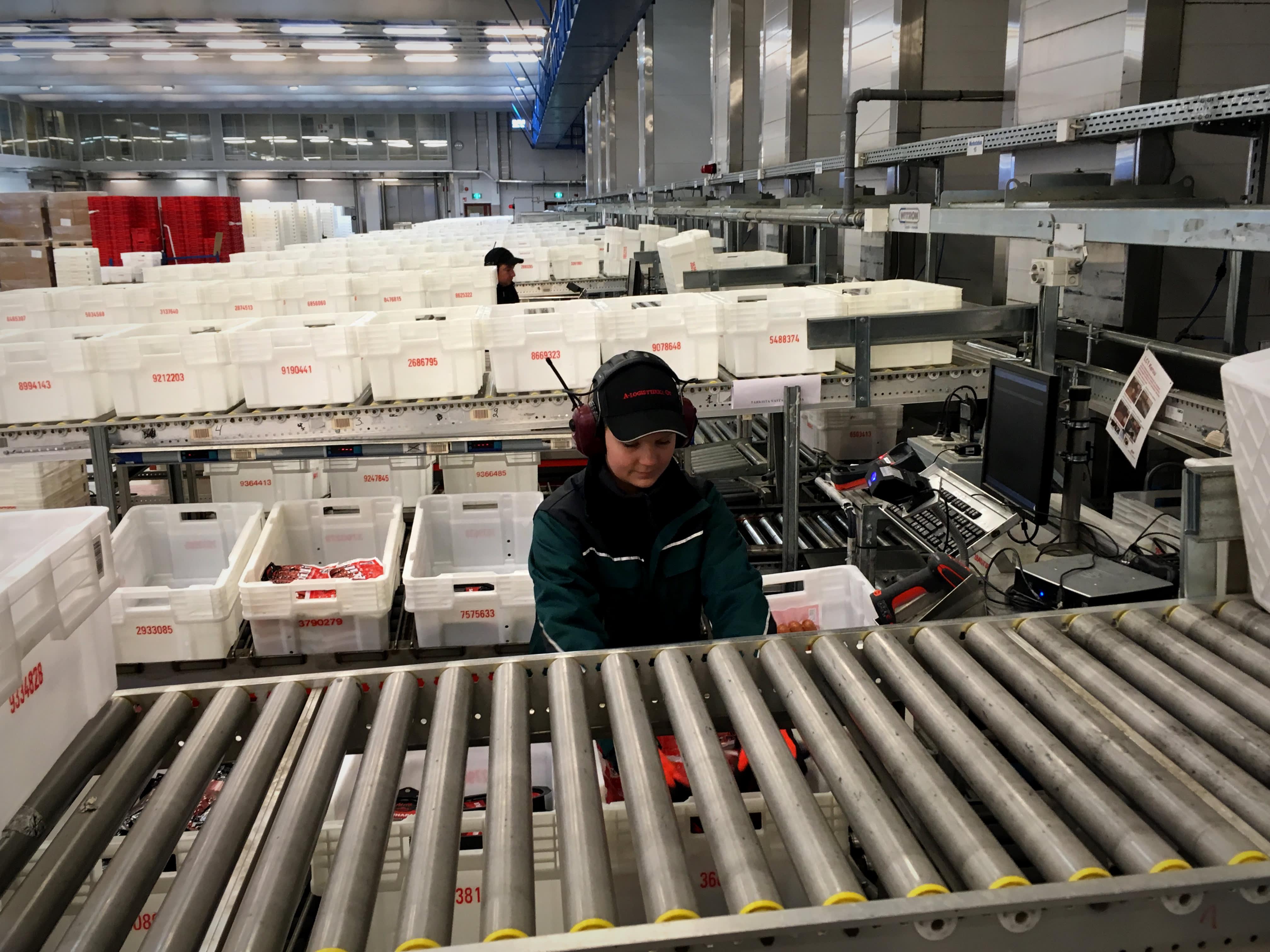 Atrian logistiikkakeskuksessa lajitellaan ruokapaketteja kuljetuslaatikoihin.