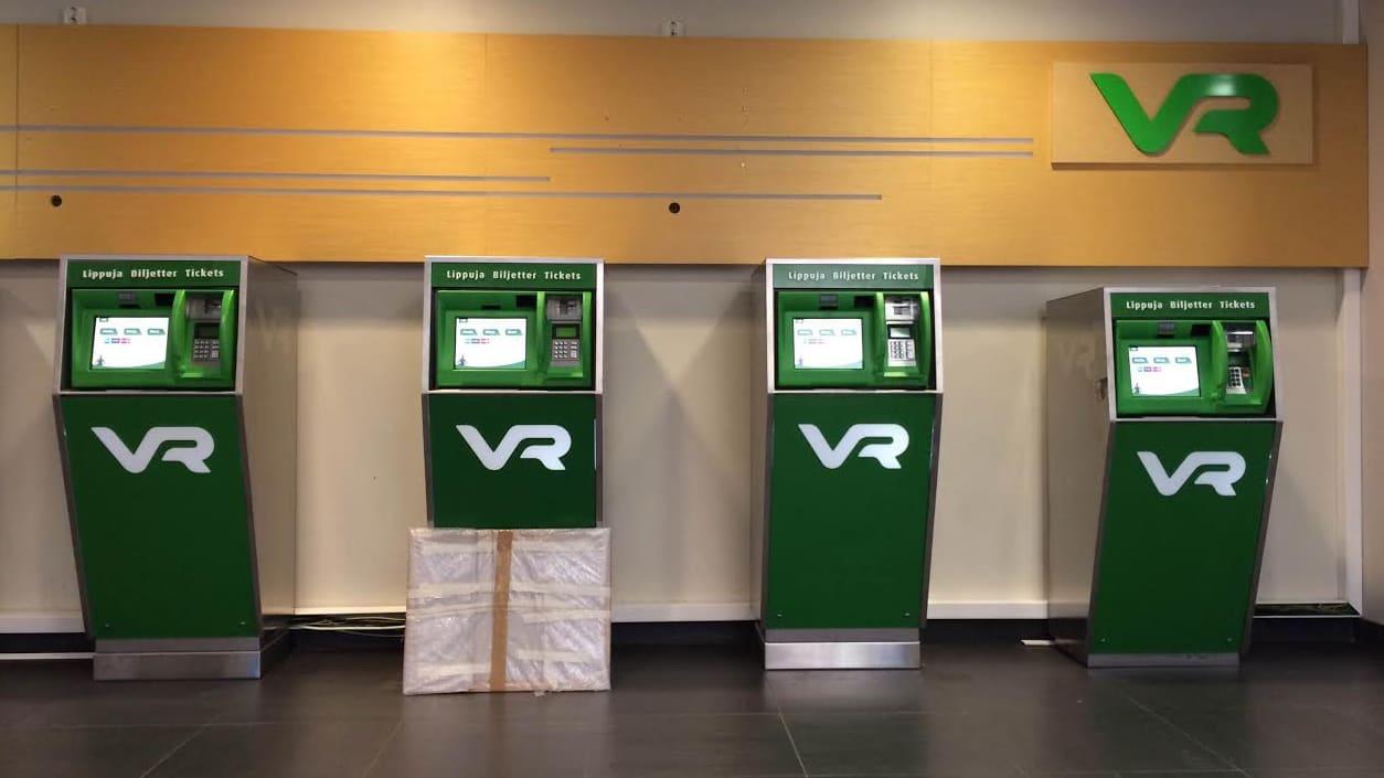 Neljä VR:n lippuautomaattia, joista yhteen nojaa yksinäinen paketti.