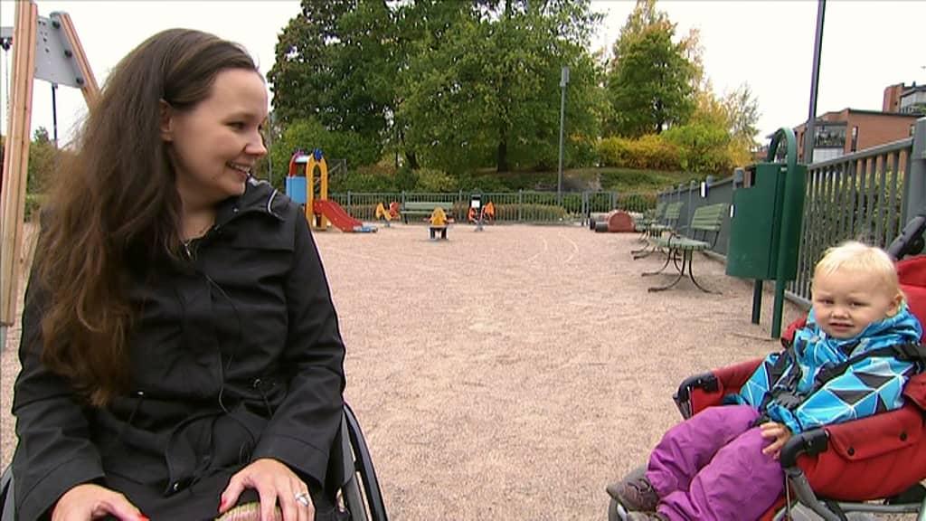 Nainen pyörätuolissa katsoo lastenrattaissa olevaa poikaansa.