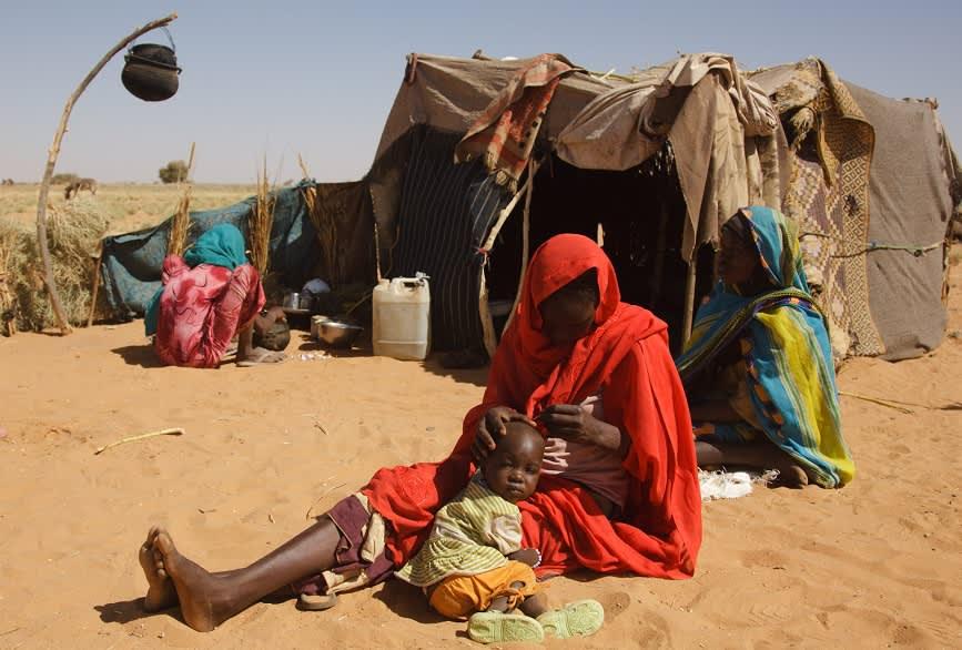 Kaksi naista ja pieni lapsi istumassa hiekalla. Takana huovista tehty teltta.
