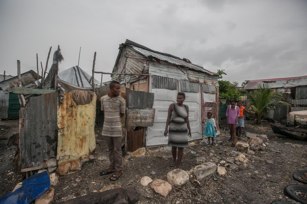 Pellinpalasista kootun hökkelin edustalla seisoo mies, nainen ja kolme lasta, taivas on aivan harmaa.