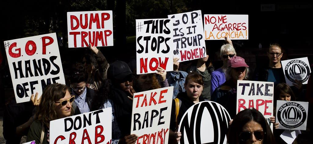 """Joukko naisia, joiden englannin- ja espanjankielisissä kylteissä lukee muun muassa: """"Tämä loppuu tähän!"""", """"Ottakaa raiskaukset vakavasti!"""" ja """"Kädet irti minusta!""""."""