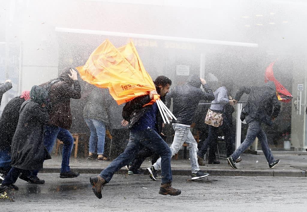 Mielenosoittajien joukko juoksee tiheässä vesisumussa  märällä kadulla.