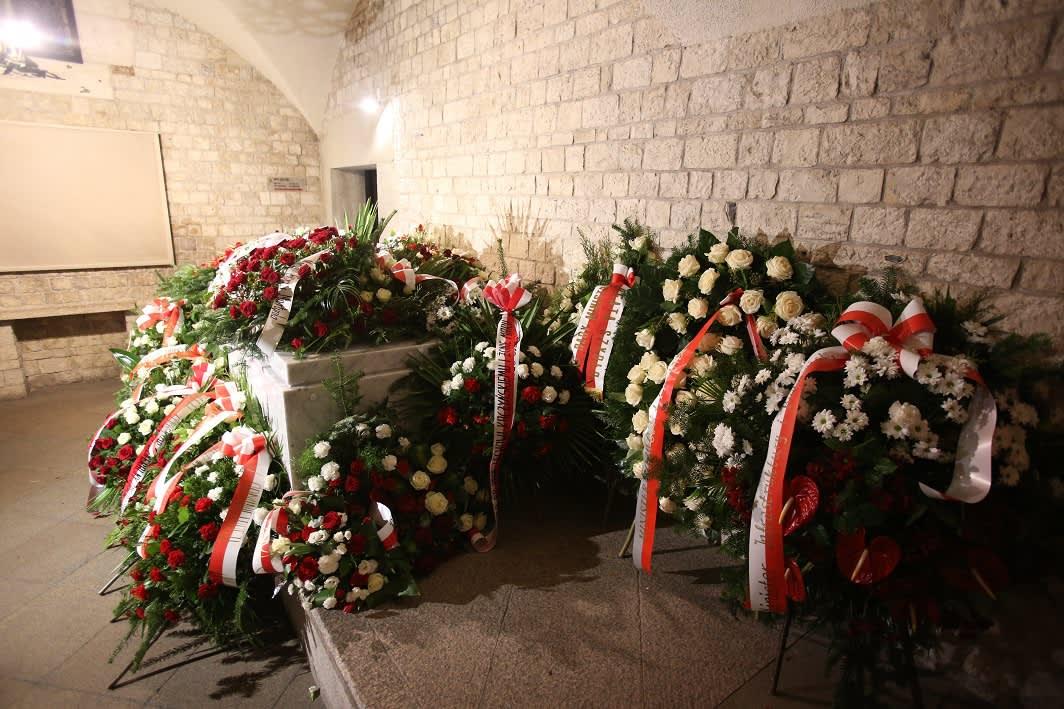 Kuvassa marmoriarkkujen päällä punavalkoisia kukkalaitteita ja nauhoja.