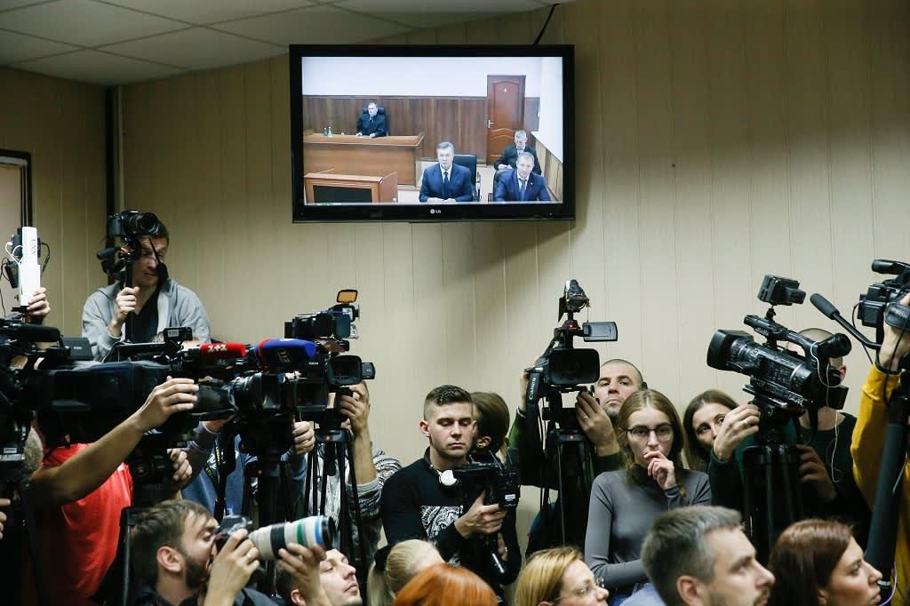 Toimittajien joukko seisoo televisioruudun alla. Ruudulla näkyy Ukrainan entinen presidentti rostovilaisessa tuomioistuimessa.