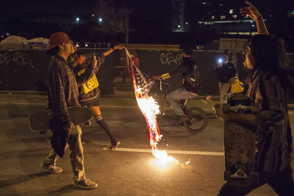 Yöllinen kuva, jossa juokseva mielenosoittaja roikottaa perässään palavaa lippua.