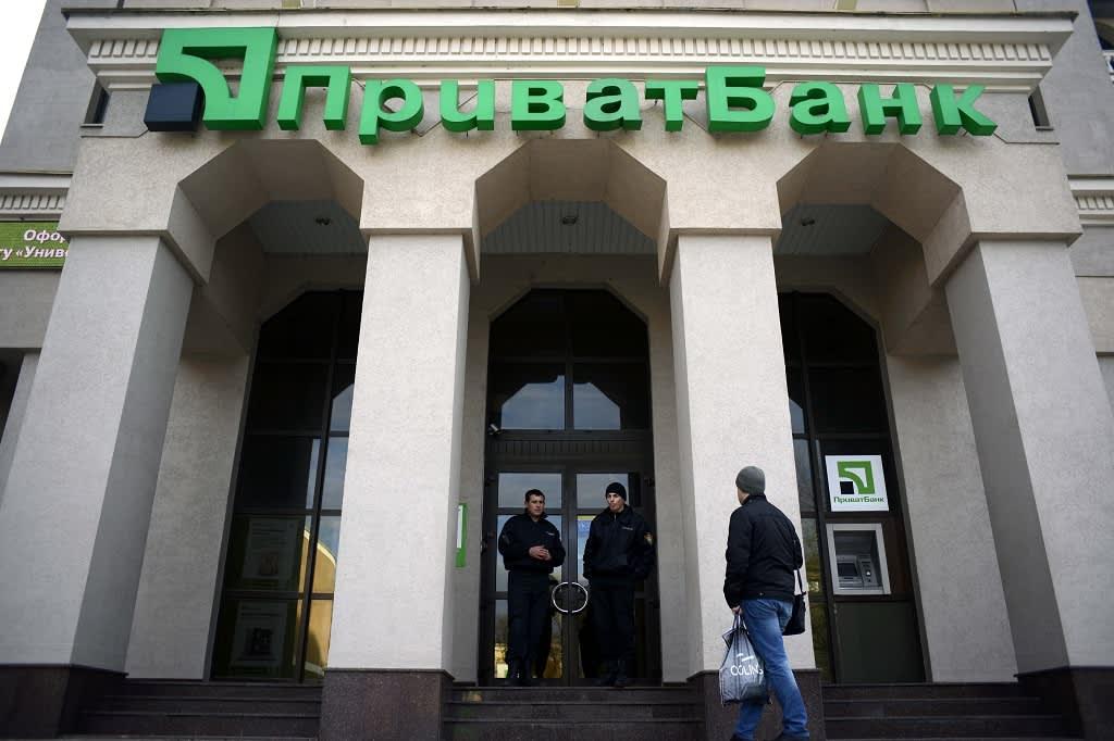 Vartijat seisovat PrivatBankin sisäänkäynnin edustalla Simferopolissa, Krimillä 17.3. 2014.