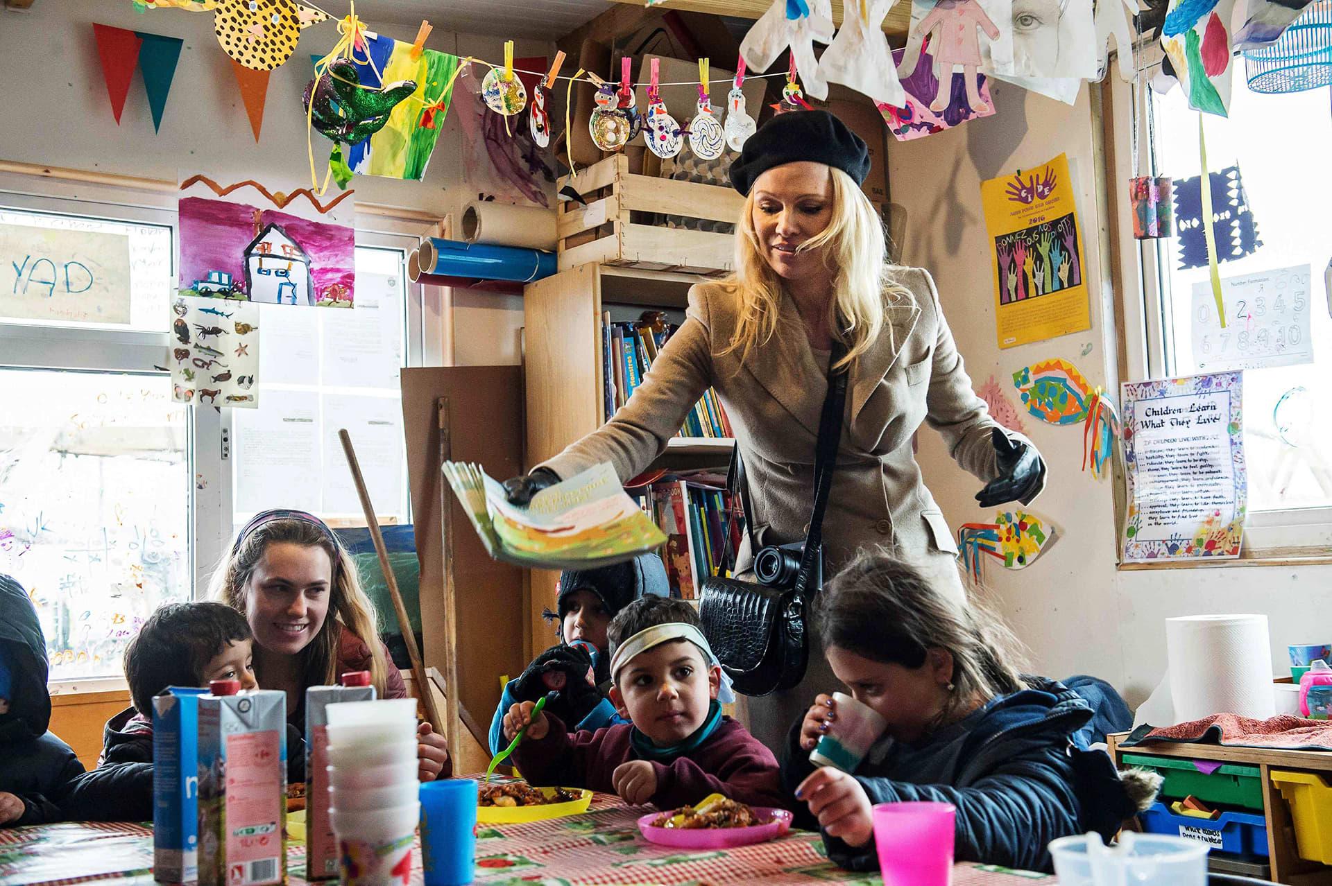 Pamela Andeson jakaa värityskirjoja pakolaislapsille.