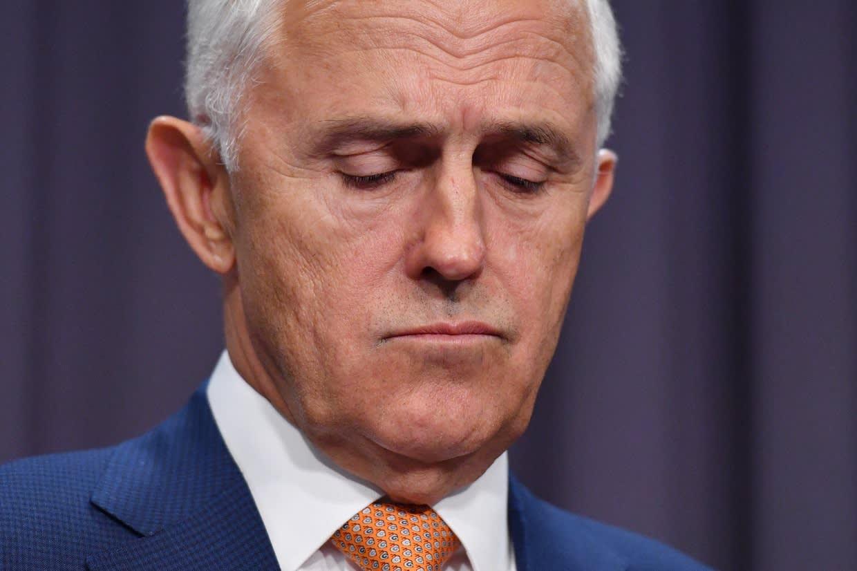 Turnbull lähikuvassa otsa rypyssä, katsoo alaviistoon.