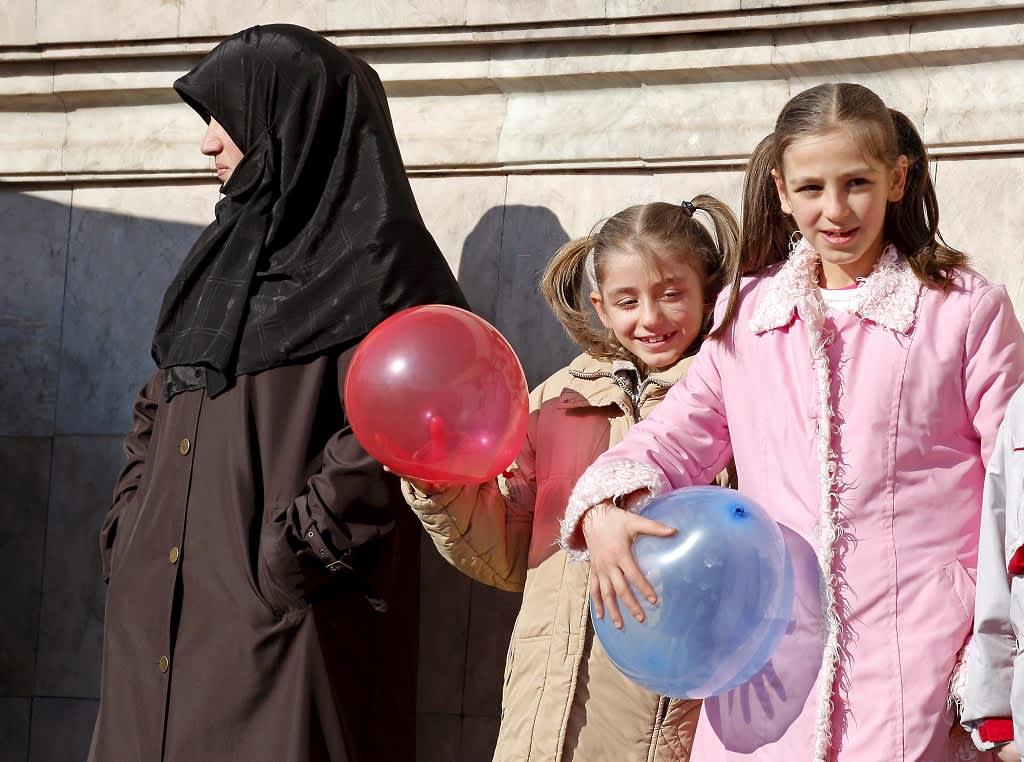 Suurella mustalla huivilla päänsä peittänyt nainen seisoo seinän vieressä. Hänen vieressään on kaksi nuorta tyttöä, joilla on palmikot päässään ja käsissään ilmapallot.