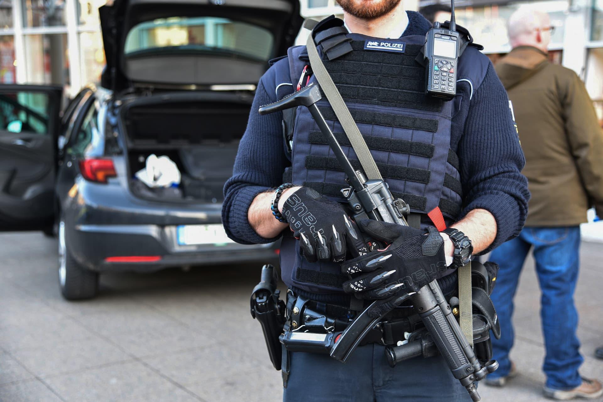 Poliisi seisoo auton edessä ase kädessä.