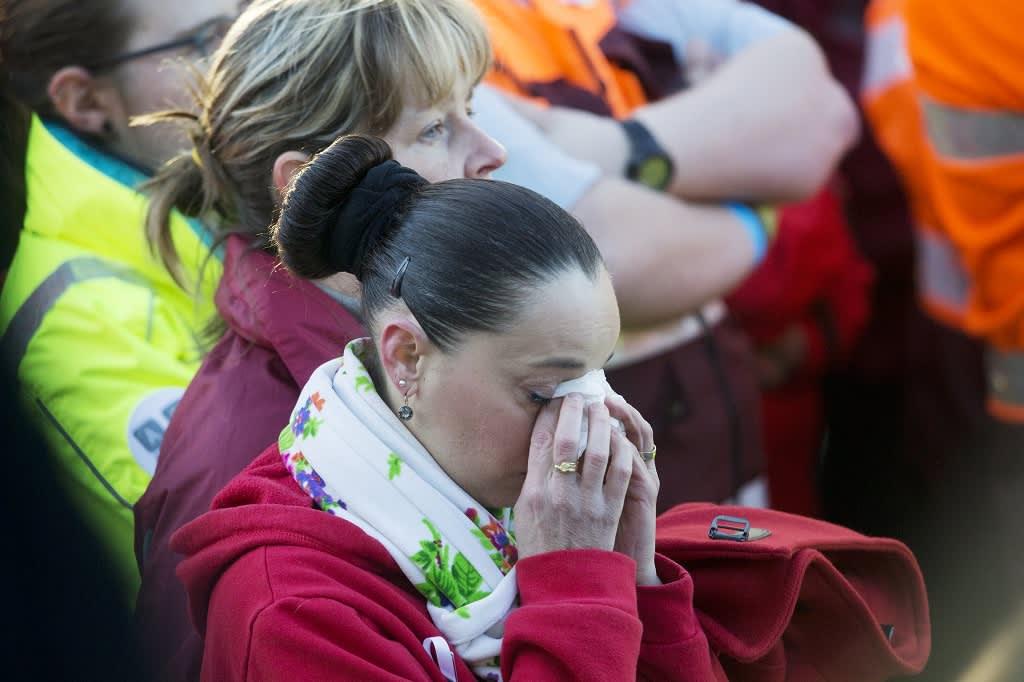 Nainen pyyhkii kyyneleitä nenäliinalla Brysselin lentokentällä järjestetyssä muistotilaisuudessa.
