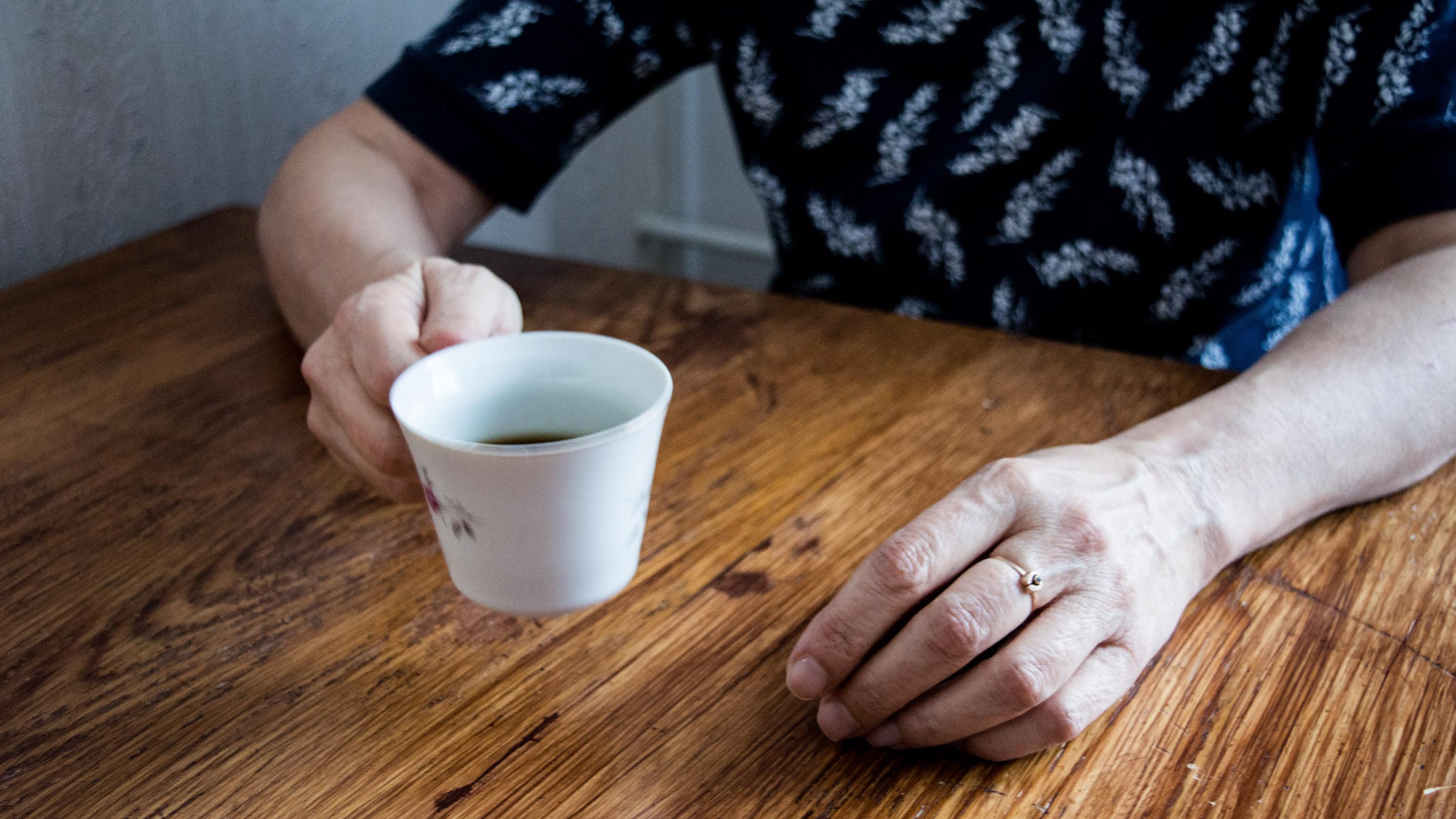 Henkilö istuu pöydän ääressä ja pitelee toisessa kädessä kahvikuppia.
