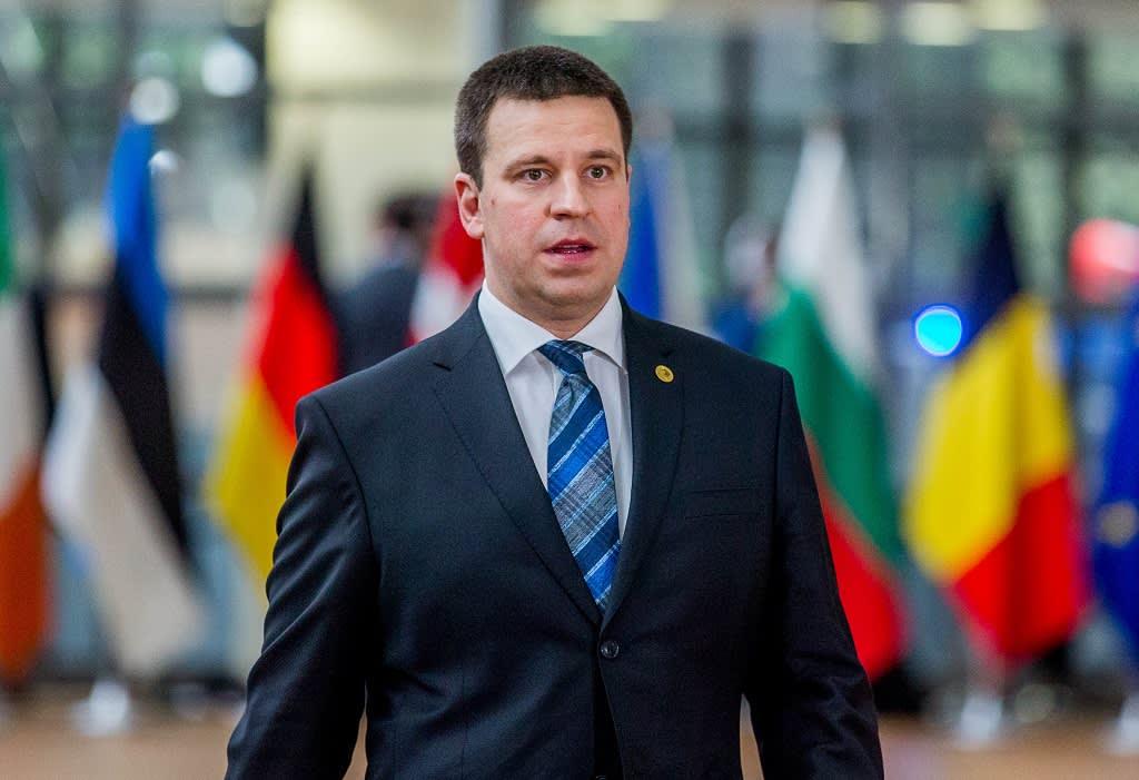 Tummaan pukuun pukeutunut Jüri Ratas, taustalla EU-maiden lippuja.