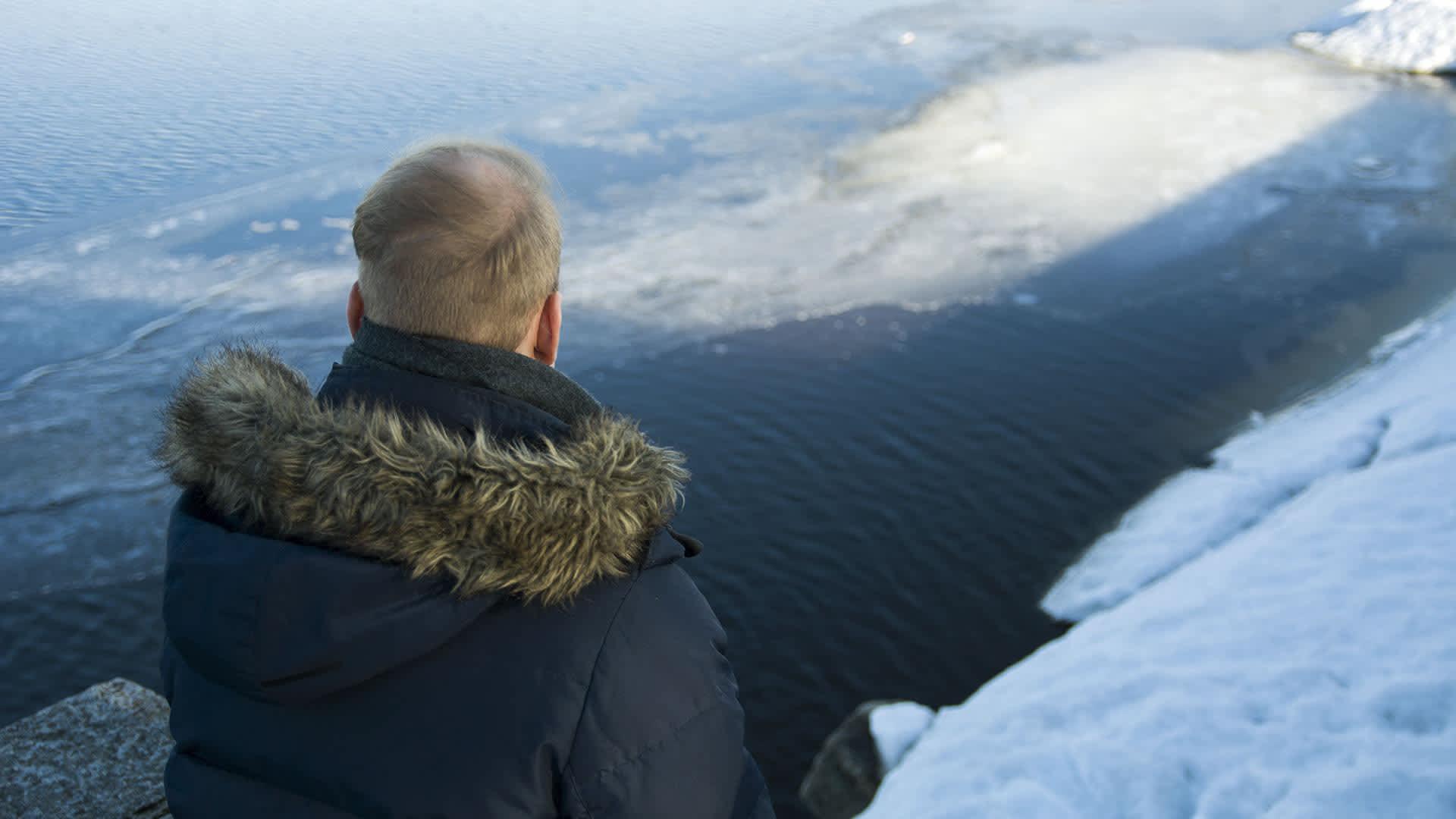 Mies katselee järvelle.