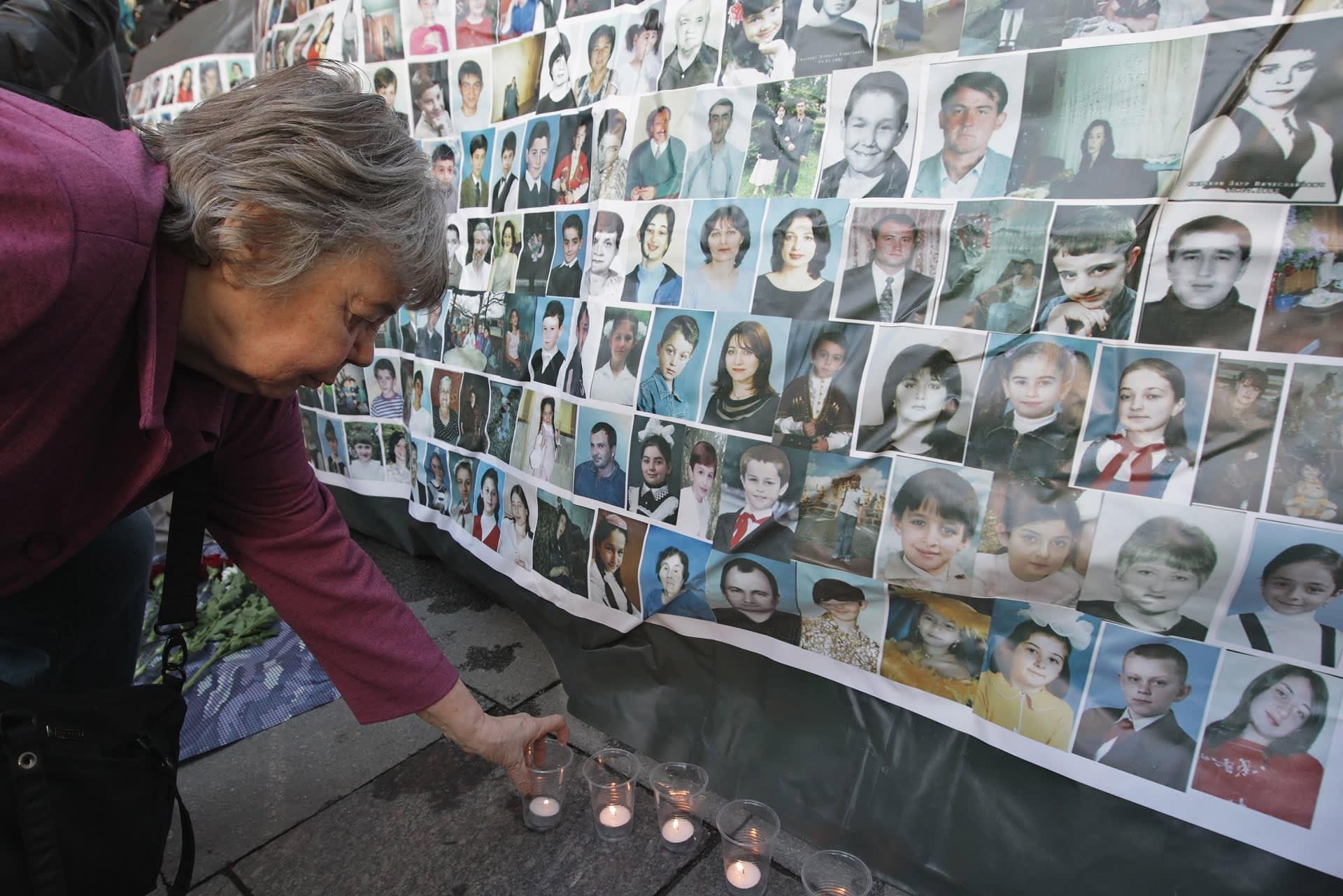 Nainen asettaa kynttilää maahan uhrien valokuvien alle.