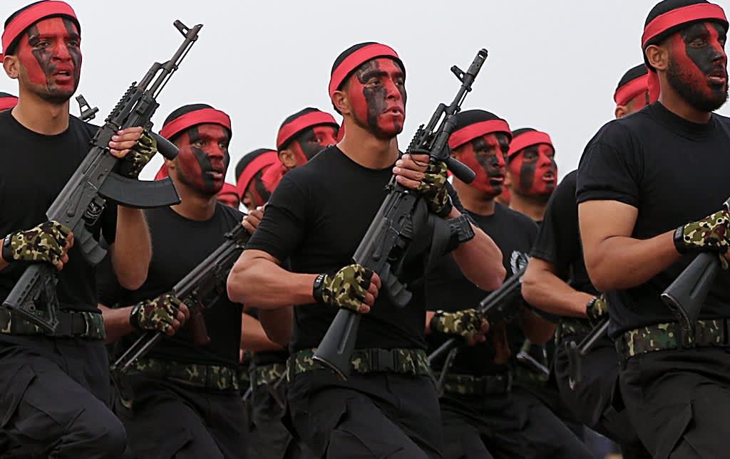 Joukko Hamasin taistelijoita marssii rynnäkkökiväärit käsissään, kasvot maalattuina punaiselle ja mustalla värillä, otsallaan punainen panta.