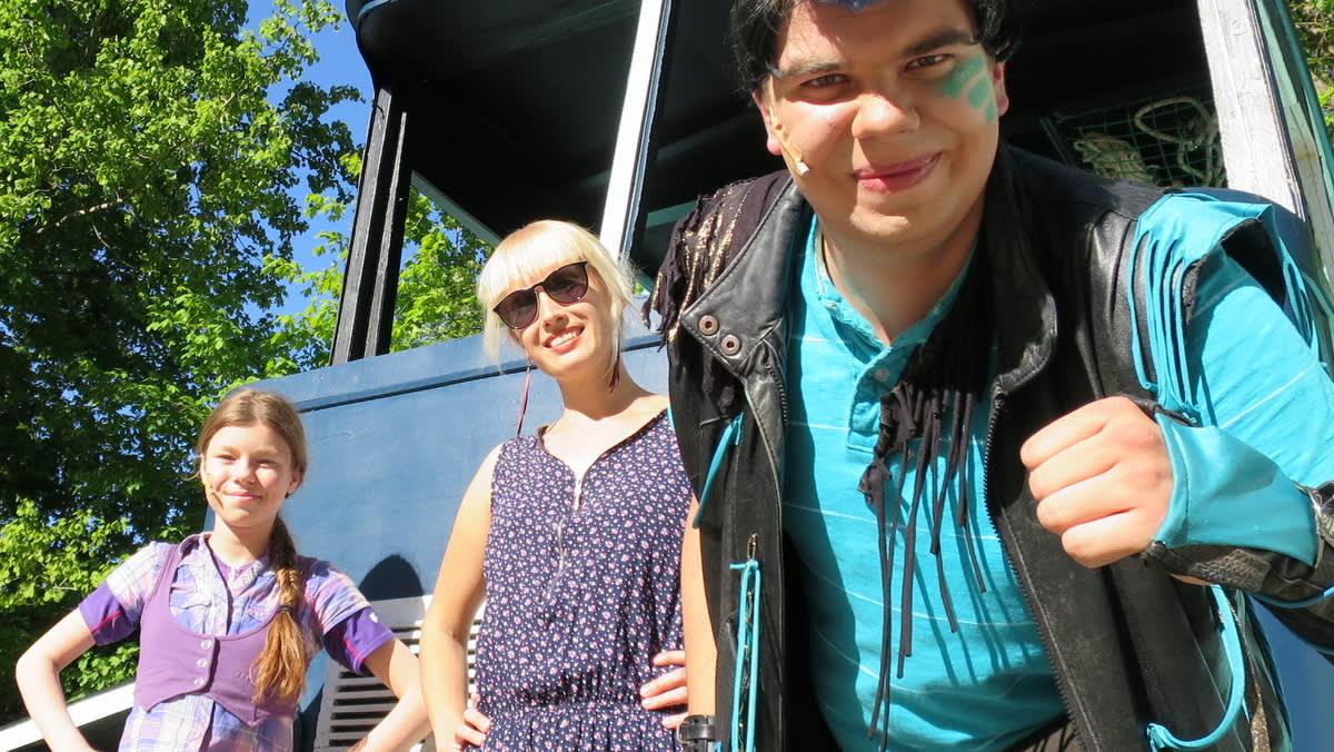 Kolme henkilöä kesäteatterin kulisseissa auringossa