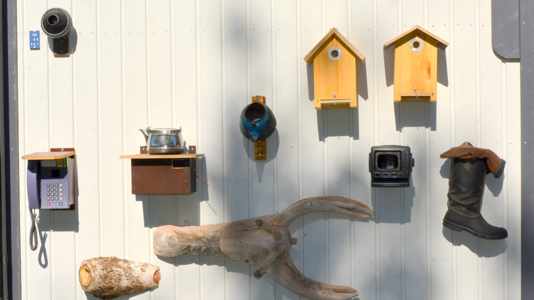 Erilaisia linnunpönttöjä seinällä.