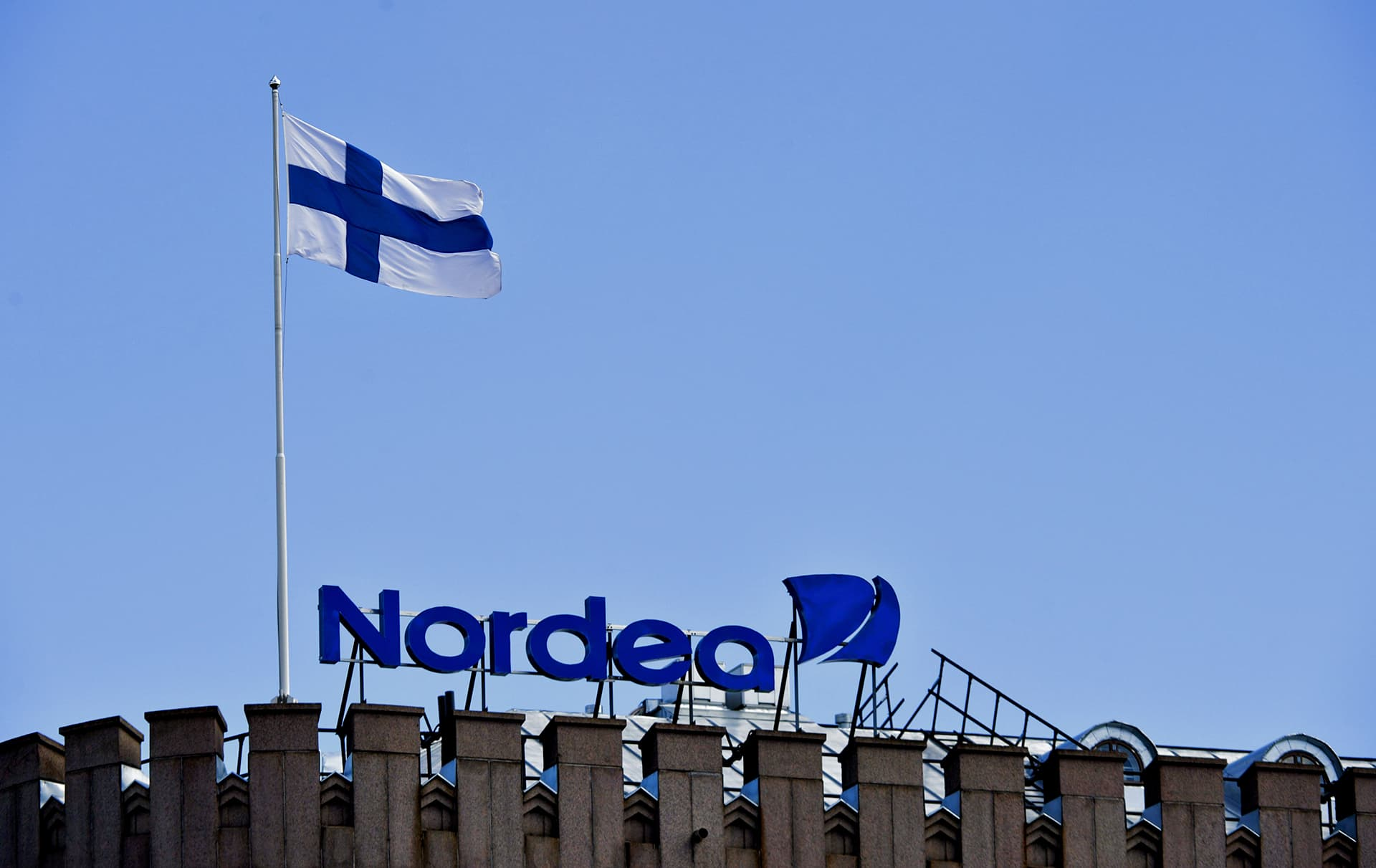 Nordean valomainos ja Suomen lippu talon katolla Helsingin keskustassa.