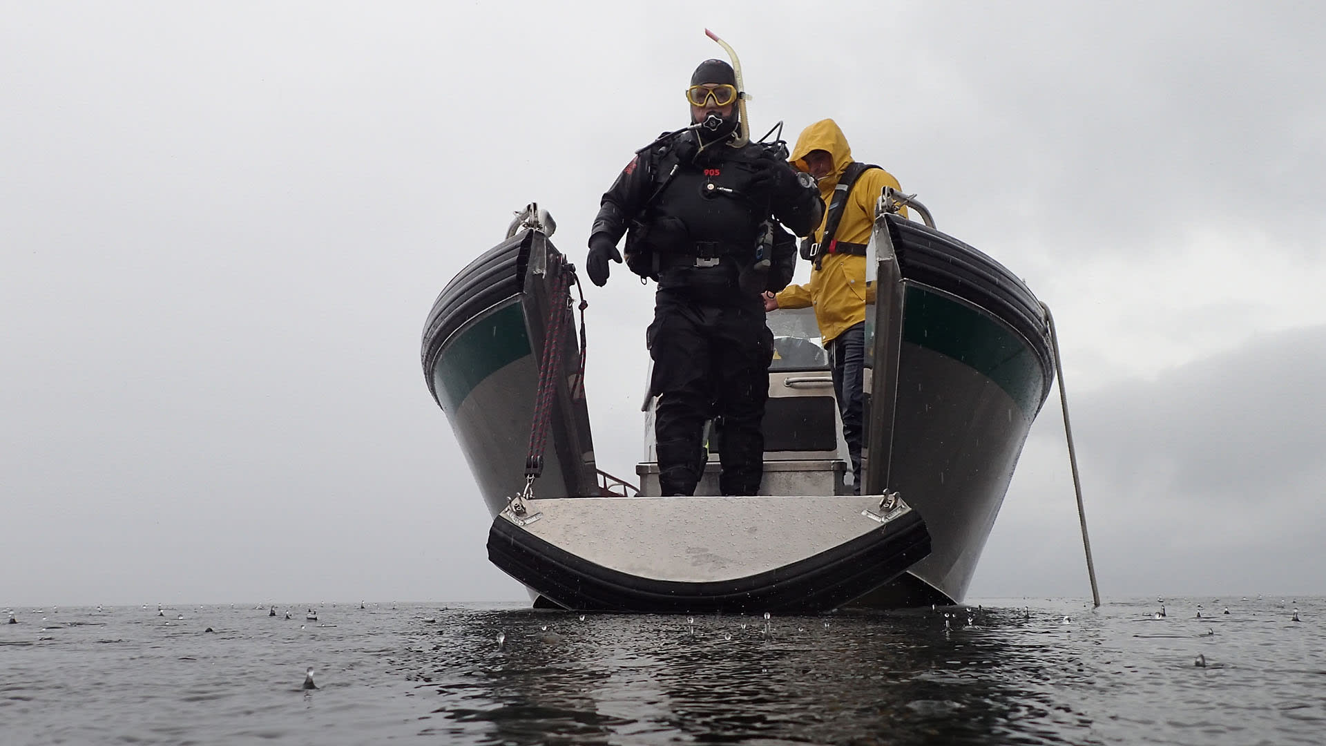 Mies sukeltamassa mereen veneestä, johon on tuunattu portti erityisesti sukeltamisen helpottamiseksi