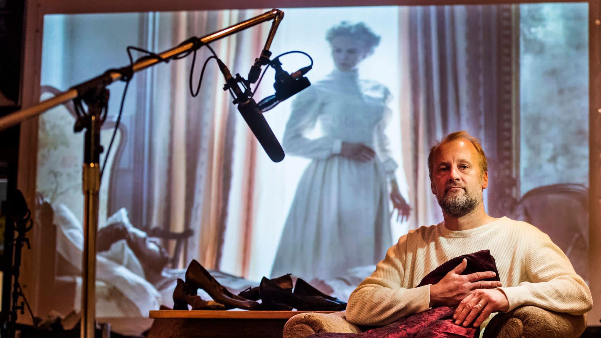 Heikki Kossi studiollaan, taustalla Nicole Kidman valkokankaalla elokuvassa Lumotut.