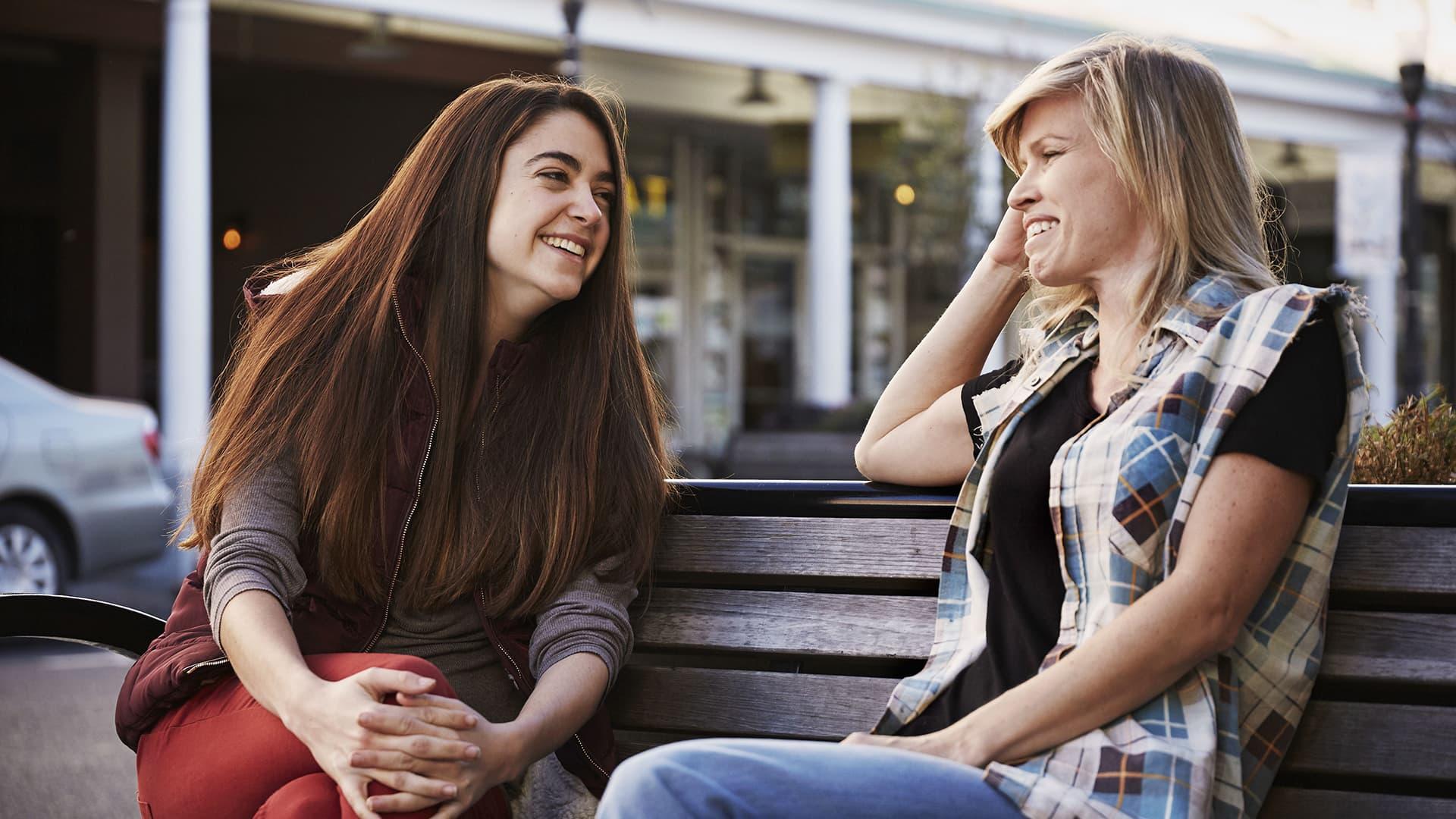 Kaksi naista istuvat penkillä ja keskustelevat toistensa kanssa.