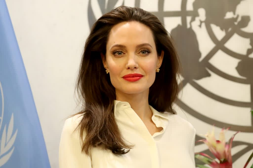 Angelina Jolie puolilähikuvassa, taustalla YK:n logo.