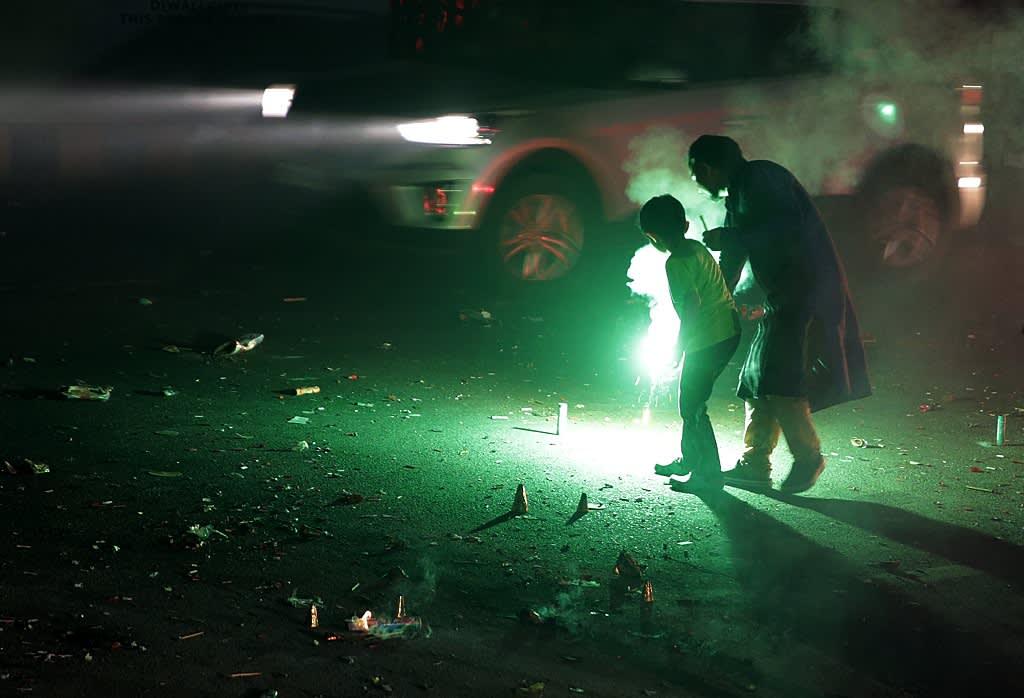 Mies ja lapsi ampuvat ilotulitteita kadulla.
