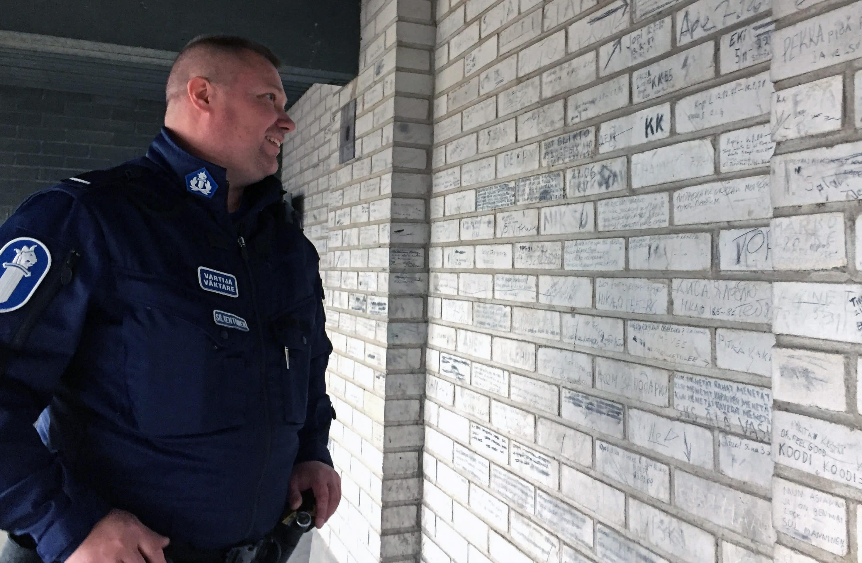 vartija lukee tekstiä tiiliseinässä
