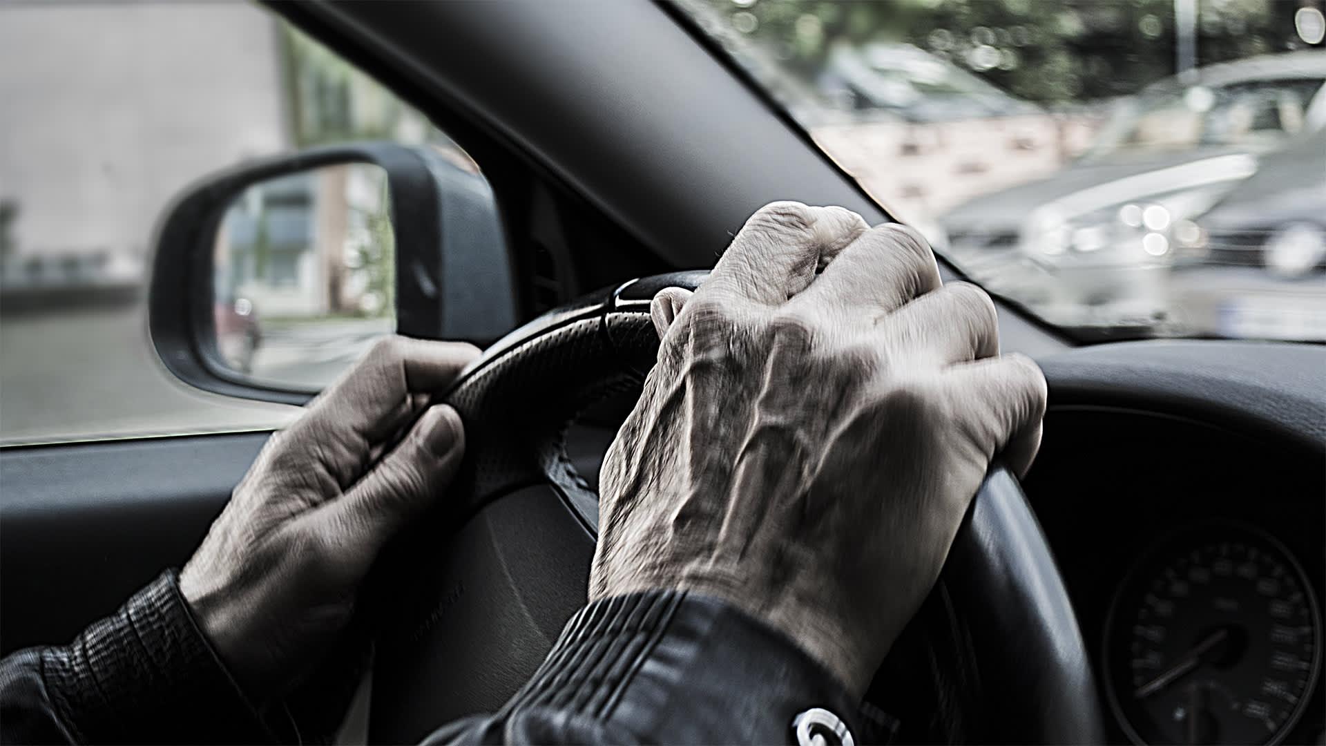 Vanha mies puristaa auton rattia käsillään.