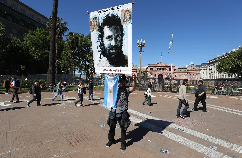 Santiaho Maldonadon kuvaa kantava mielenosoittaja kadulla.